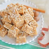 Gingerbread fudge on a white plate with a cookies cutter and cinnamon sticks