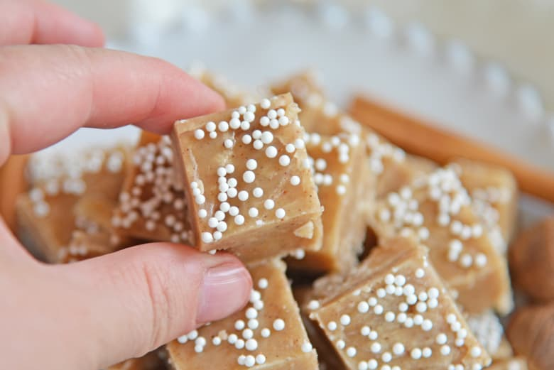 Hand picking up a square of gingerbread fudge