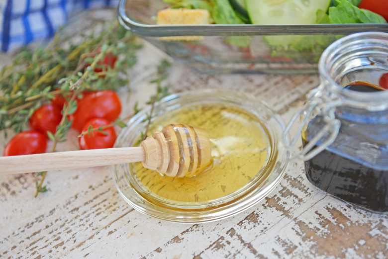 Honey on a tray with salad in the background