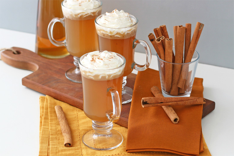 Cups of hot buttered rum and cinnamon sticks