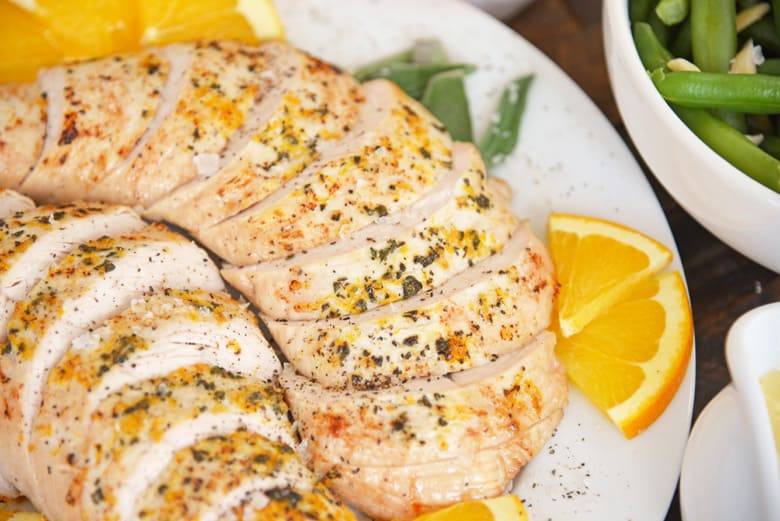 Closeup of sliced turkey breast with orange and sage