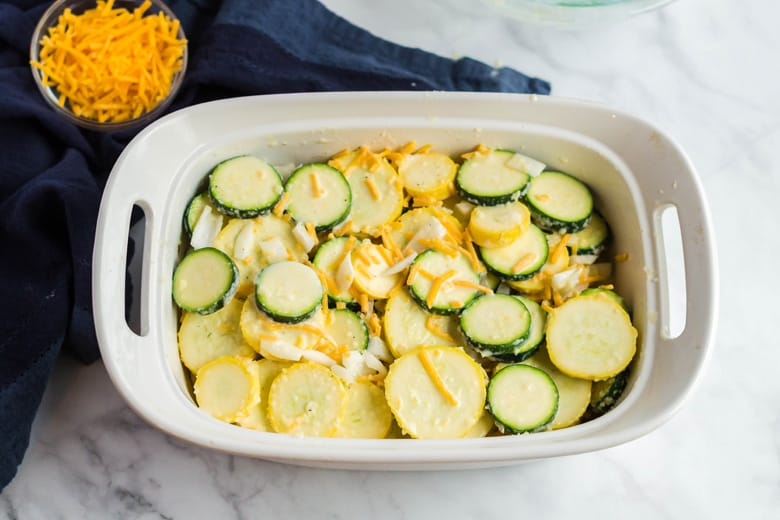 Layering yellow and green squash with cheese