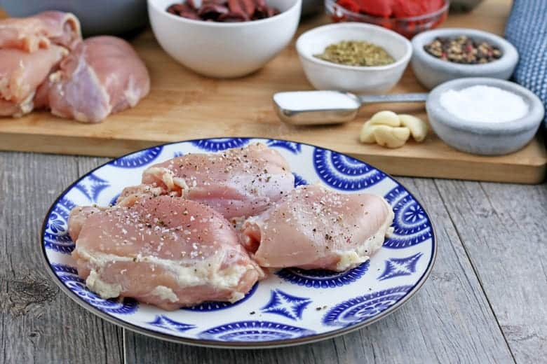 Raw seasoned chicken on a blue and white plate