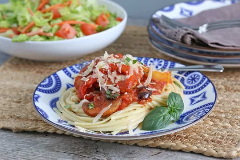 Chicken cacciatore over spaghetti on a blue and white plate.