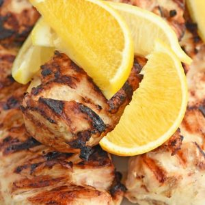 close up of lemon wedges with grilled chicken