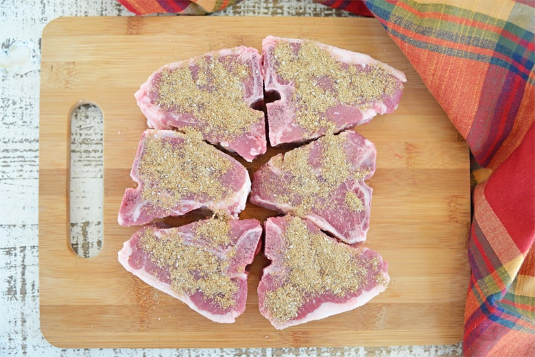 Seasoned lamb chops o a wood cutting board
