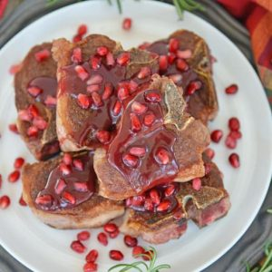 pomegranate lamb chops on a white platter