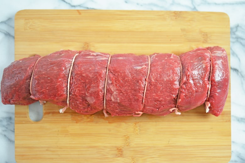 Center cut beef tenderloin tied with butcher's twine on a cutting board