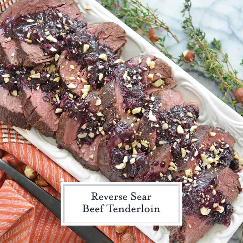 Overhead of sliced reverse sear beef tenderloin with a blueberry sauce and toasted hazelnuts