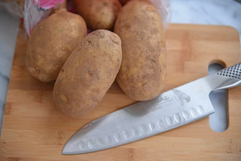 Russet potatoes on a cutting board for chopping