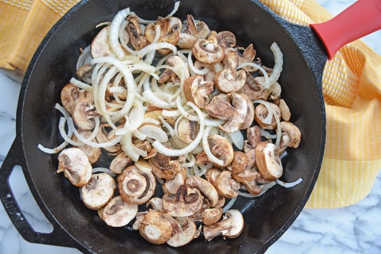 Mushrooms and onions in cast iron pan for gravy