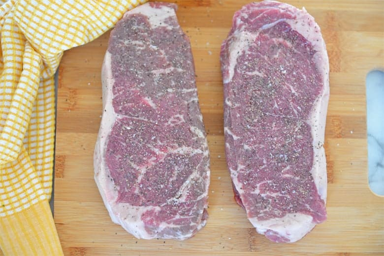Seasoned strip steaks on a cutting board