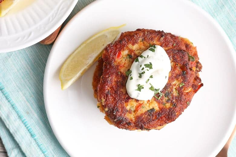 Overhead of salmon cakes with a lemon slice on a white plate
