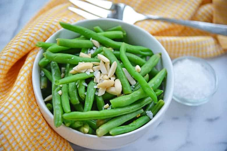 Steamed green beans with almonds and salt in a white serving bowl