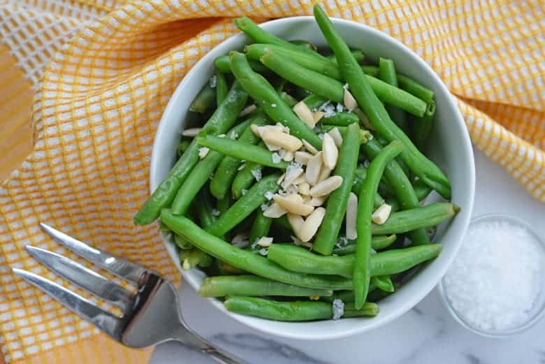 Side of steamed green beans with a serving fork