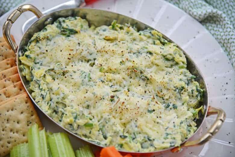 Cooked spinach artichoke dip in a copper pot