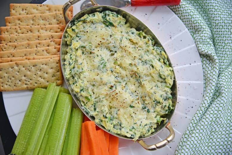 Overhead of best spinach artichoke dip with carrots and celery with crackers