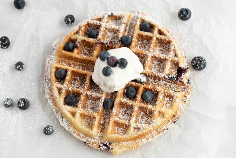 Blueberry waffle with powdered sugar and whipped cream
