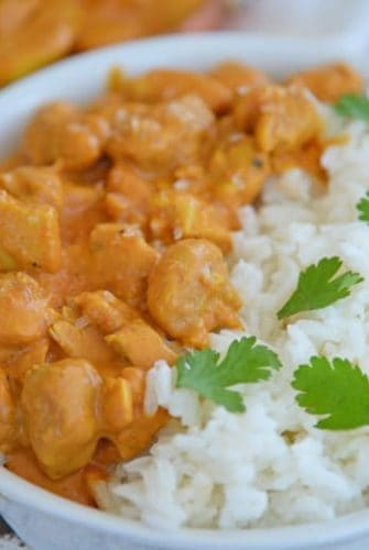 A bowl of rice on a plate, with Butter and Chicken