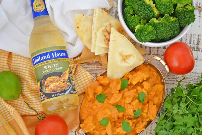 Butter chicken in a copper serving dish with fresh ingredients
