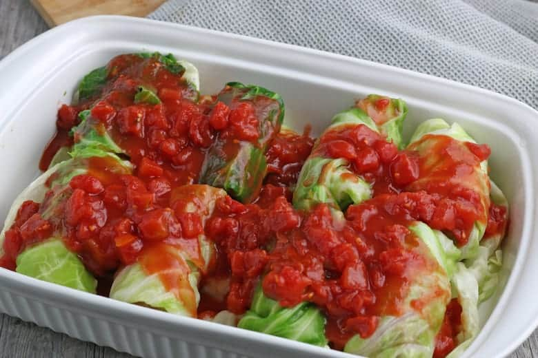 Cabbage rolls in a baking dish topped with tomato sauce