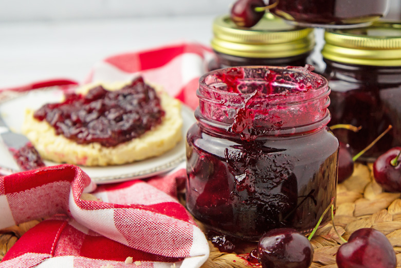 cherry jam in a mason jar and jam on a muffin