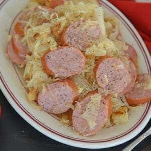 A plate of food on a table, with Kielbasa and Sauerkraut
