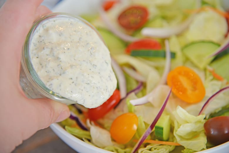 Ranch dressing pouring onto a salad