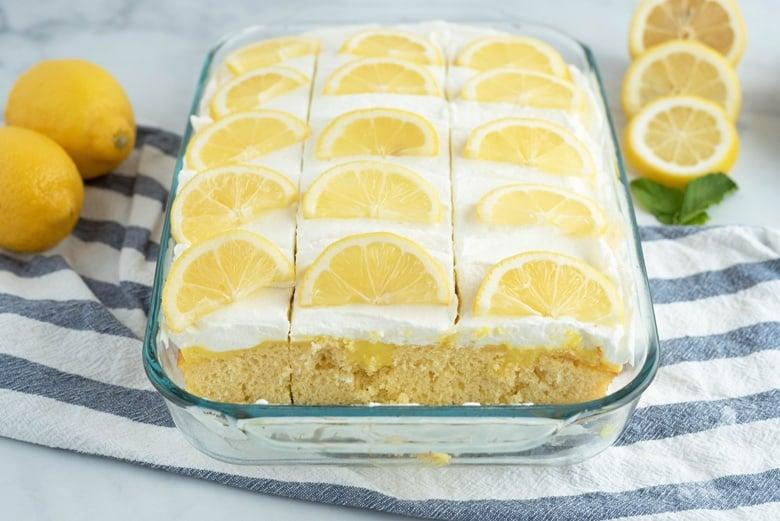 Lemon poke cake decorated with fresh lemon wedges