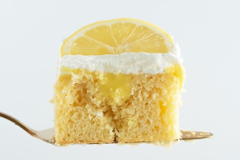 Slice of lemon poke cake on a spatula