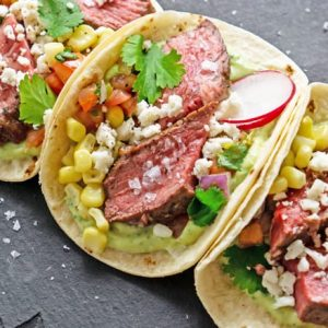 A close up of a plate of food, with Steak and Taco