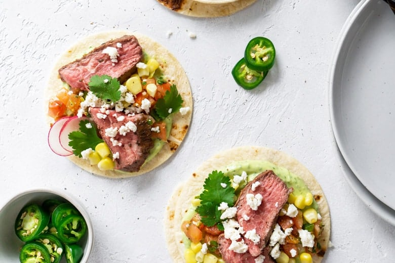 flank steak tacos on a white board