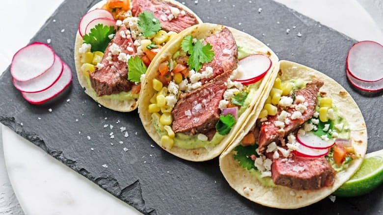 Serving platter of flank steak tacos with radish slices