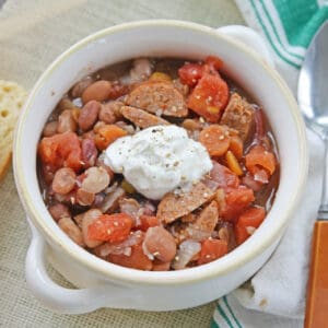 15 bean soup in a white bowl with sour cream topping