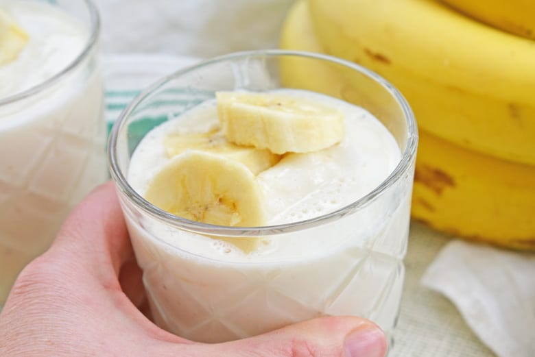 hand grabbing for banana smoothie in a glass