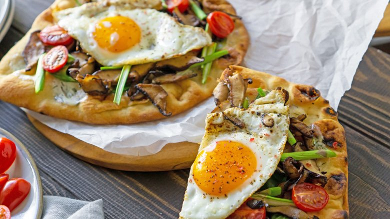 Breakfast pizza with vegetables and runny egg