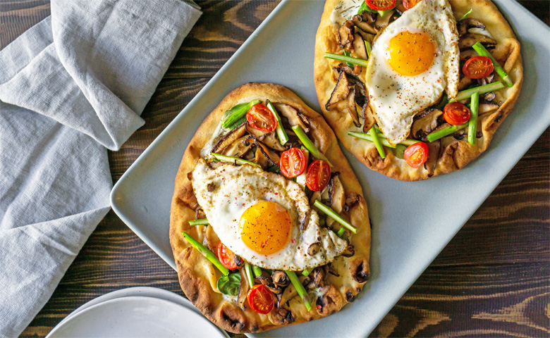 Two individual breakfast pizzas with egg
