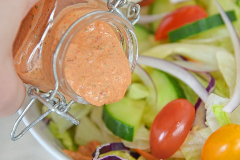 homemade chipotle ranch dressing pouring onto salad