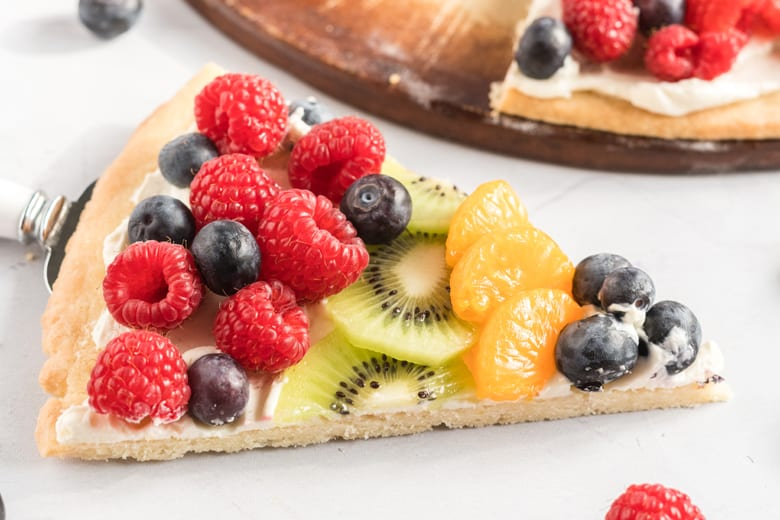slice of dessert pizza with fresh fruit including raspberries, blueberries, kiwi and oranges