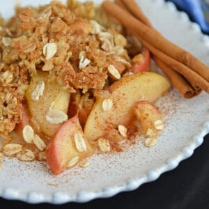white plate of apple crisp with oatmeal crumble topping