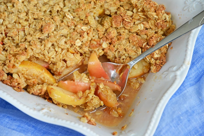 spooning out hot apple crisp