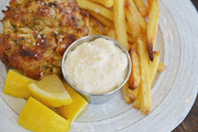 horseradish aioli dipping sauce with a crab cake, french fries and lemons