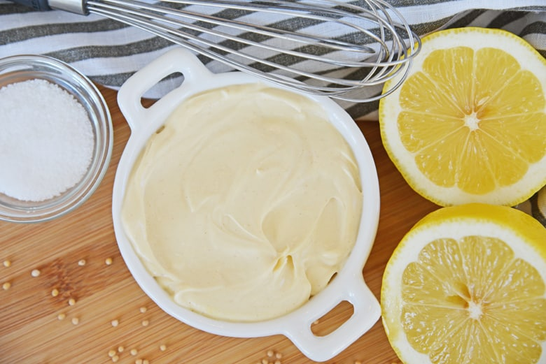 mustard aioli sauce in a white bowl with lemon and a whisk