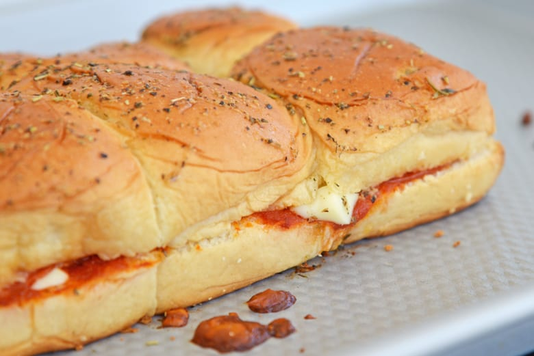 Baked pizza sliders on a baking sheet