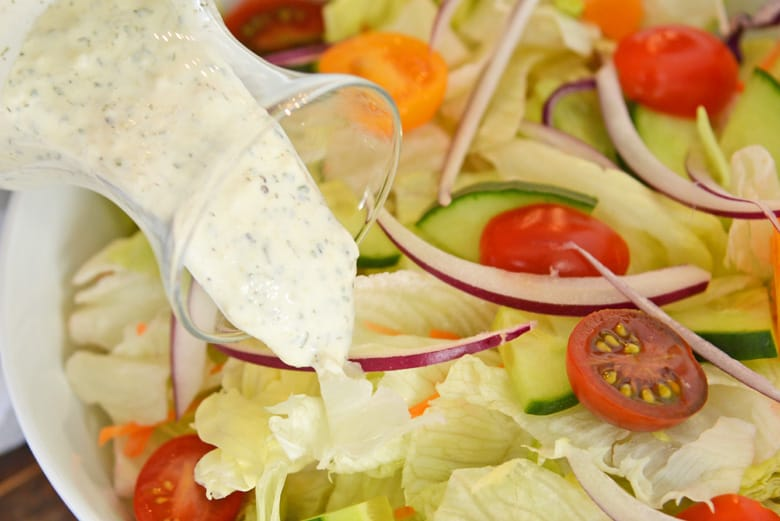 Ranch dressing pouring over fresh salad