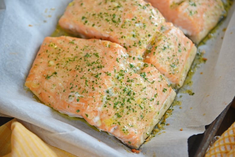 pieces of seasoned salmon on a parchment lined baking sheet