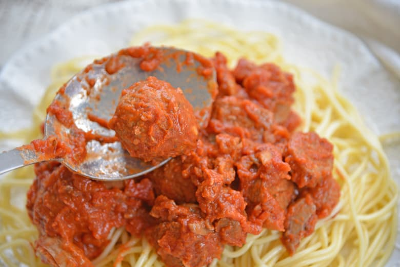 spooning a homemade meatball onto a plate of spaghetti