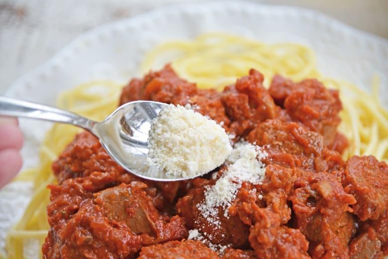 spooning parmesan cheese onto spaghetti sauce