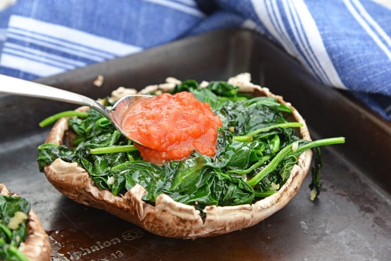 marinara sauce spooning over spinach in a mushroom cap