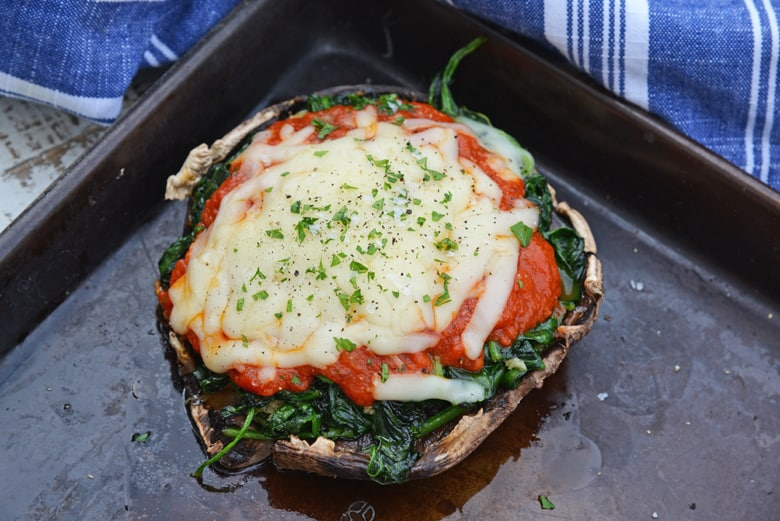 melted cheese on spinach stuffed mushrooms